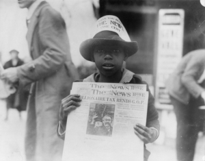 A little boy selling newspapers, 1921.