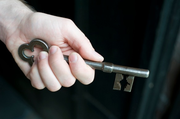 Hand holding a metallic vintage key