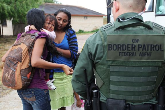 An infant cries as U.S. Border Patrol agents process a group of immigrants in Granjeno, Texas, outside of McCallen on June 25, 2014.