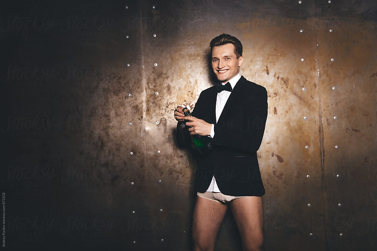 A young white man wearing a tuxedo jacket, white shirt, black bow tie, white underwear, and a smile. He's opening a bottle of champagne because of course he is.