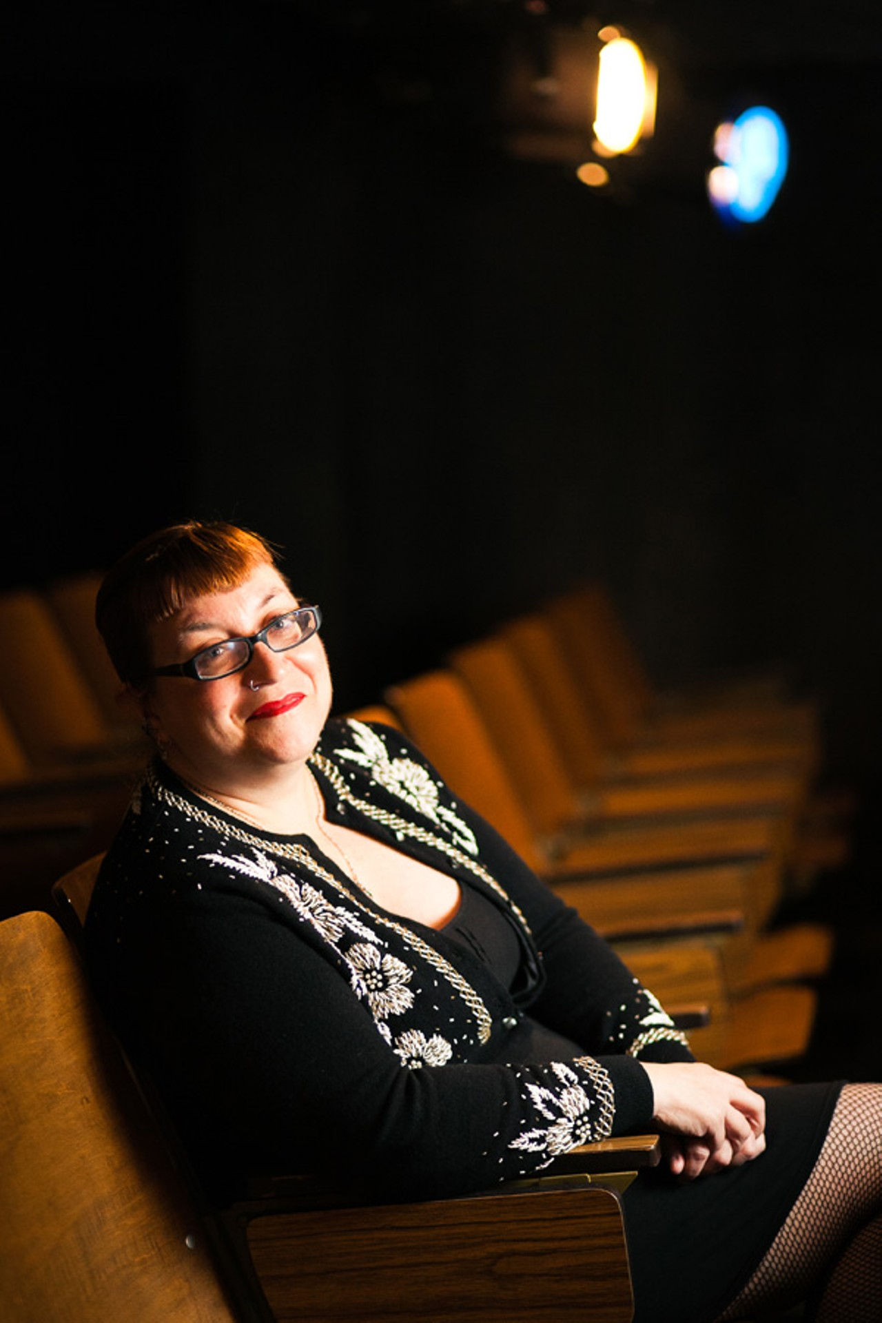 A smiling redhead wearing a black beaded sweater, a black dress, black-framed glasses, and red lipstick sits in a theater with her hands folded in her lap.
