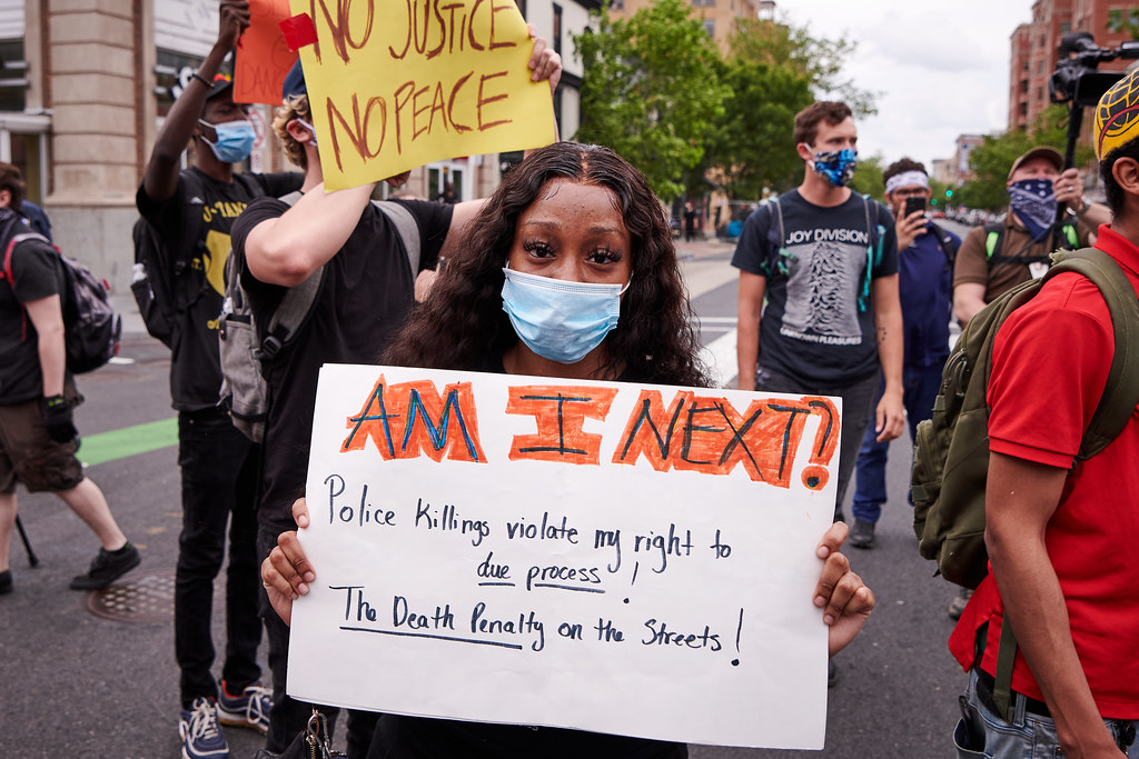 "A young Black woman with long, wavy hair parted in the middle, stands at a protest, wearing a face mask and holding a sign that says: ""AM I NEXT? Police killings violate my right to due process! The Death Penalty on the streets!"""