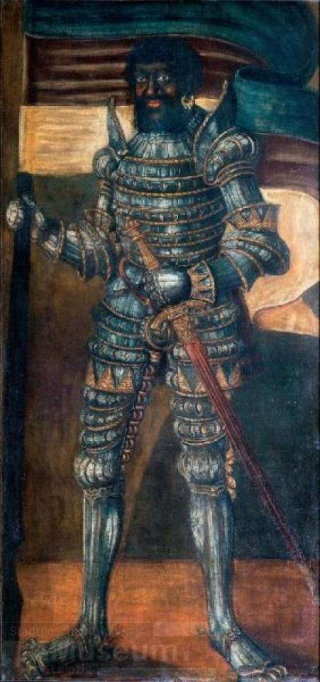 A Black man in spectacular full armor.  His helmet is off, so you can see his bearded face. He holds his sword in his left hand and a standard in his right. His body is angled away, but he looks straight out at the viewer.