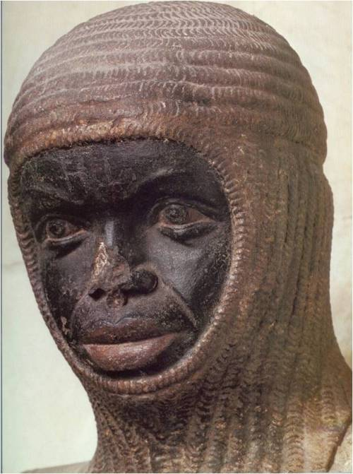 The head of a Black man wearing a chain mail coif. The statue's nose is slightly damaged.
