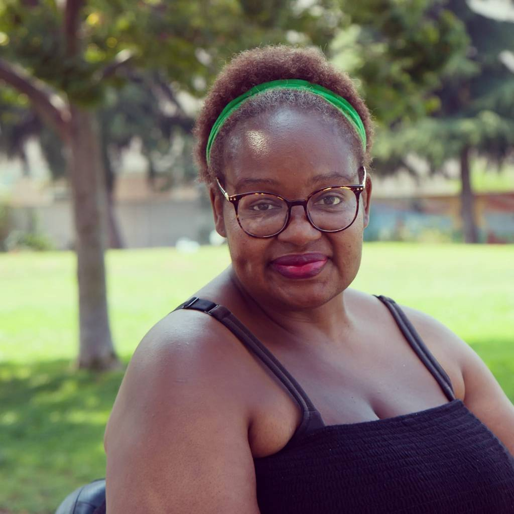 A Black woman with short hair, a green headband, tortoise-shell-framed glasses, a black spaghetti-strap top, and pink lipstick smiles cutely, showing off her dimple. She's seated outdoors in a lovely park with green grass and trees.