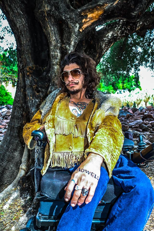 A man sits in his wheelchair outside in front of a large tree. He has long, curly drak hair, olive skin, and a beard. His mustache has been waxed to curl up at the ends. He wears large, 70s-style sunglasses, a dark yellow suede coat with a fur-lined hood and fringe at the chest and waist, and blue jeans. He has one hand on the wheelchair armrest and one on his knee.  He has tattoos on his chest and hand, and a serious expression on his face.