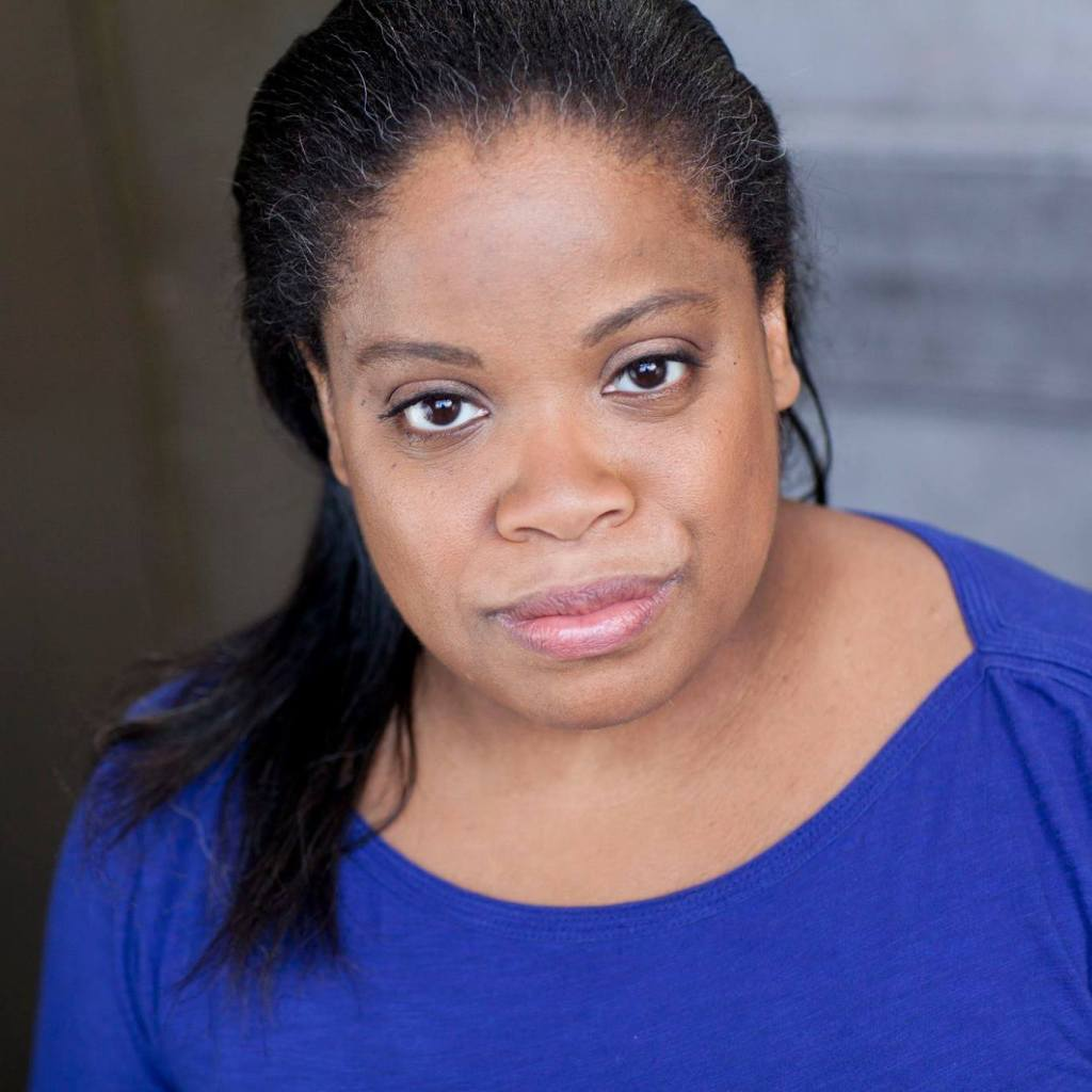 A Black woman with her hair pulled back and falling over one shoulder smiles slightly in this headshot. She wears a rich blue shirt and light pink lipstick. She leans toward the camera as if she's about to tell a fascinating story.